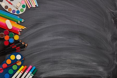 Stationery accessories: paint, pensils, crayons on background of school blackboard. Top view, copy space. School accessories for childrens education and development. Art lesson or drawing