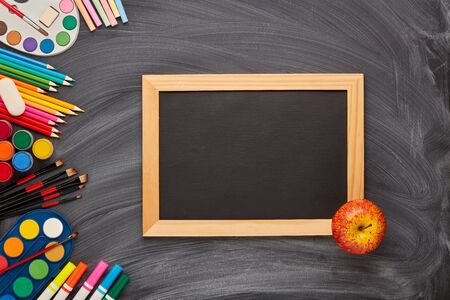 Blank black board, apple and stationery accessories on background of school blackboard. Top view, copy space. School accessories for childrens education and development. Art lesson or drawing