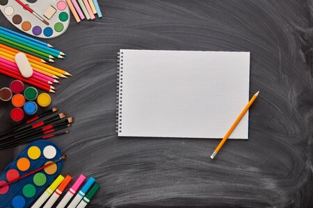 Blank sheet of writing-book and stationery accessories on background of school blackboard. Top view, copy space. School accessories for childrens education and development. Art lesson or drawing