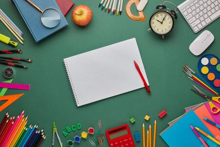 Blank writing-book, alarm clock, computer keyboard, calculator and stationery accessories on green background. Top view, copy space. School accessories for education and development. Office supplies Zdjęcie Seryjne