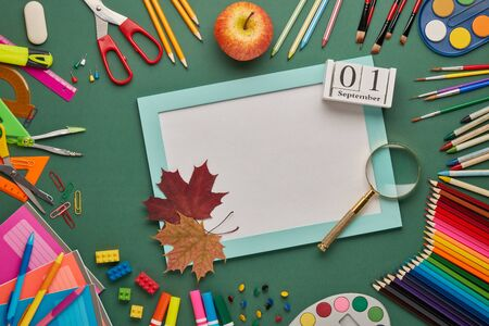 Blue frame with blank sheet, autumn leaves, stationery accessories on green background. Top view, copy space. School accessories for childrens education and development. Day of knowledges, Zdjęcie Seryjne