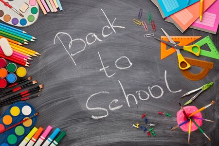 Stationery accessories on background of school blackboard with inscription: Back to school. Top view. School accessories for childrens education and development.  Office supplies.