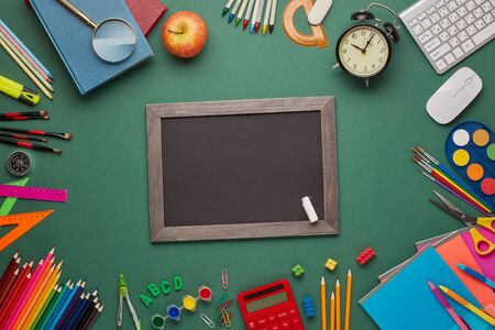 Blank blackboard, alarm clock, computer keyboard, calculator and stationery accessories on green background. Top view, copy space. School accessories for education and development. Office supplies
