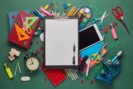 Black clipboard with blank sheet, computer tablet, microscope and stationery accessories  on green background. Top view, copy space. School accessories for education and development. Office supplies Zdjęcie Seryjne