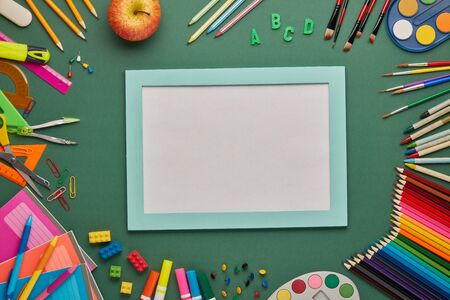 Blue frame with blank sheet and stationery accessories on green background. Top view, copy space. School accessories for education and development. Office supplies