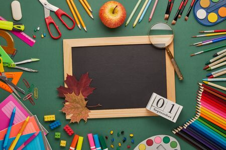 Blank blackboard, autumn leaves, stationery accessories on green background. Top view, copy space. School accessories for childrens education and development. Office supplies. Day of knowledges, Zdjęcie Seryjne