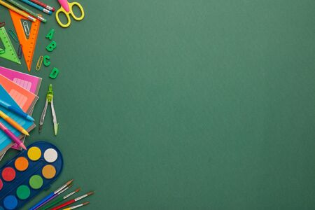 Stationery accessories on green background. Top view, copy space. School accessories for education and development. Office supplies