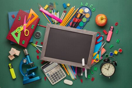 Blank blackboard, microscope and stationery accessories: pencils, pens, other office supplies on green background. Top view, copy space.  School accessories  for childrens education and development Zdjęcie Seryjne