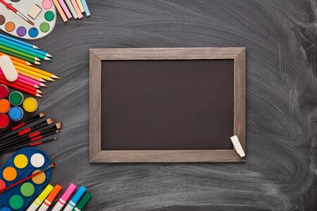 Blank black board and stationery accessories on background of school blackboard. Top view, copy space. School accessories for childrens education and development. Art lesson or drawing