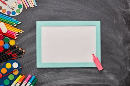 Blue frame with blank sheet and stationery accessories on background of school blackboard. Top view, copy space. School accessories for childrens education and development. Art lesson or drawing