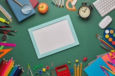 Blue frame with blank sheet, alarm clock, computer keyboard and stationery accessories on green background. Top view, copy space. School accessories for education and development. Office supplies Zdjęcie Seryjne