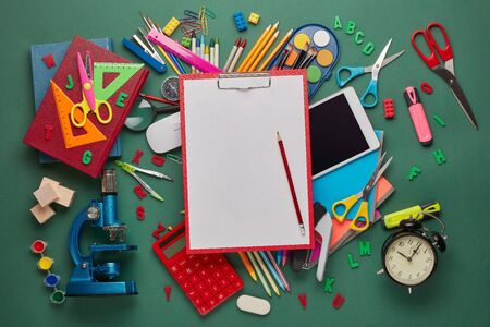 Red clipboard with blank sheet, computer tablet, microscope and stationery accessories  on green background. Top view, copy space. School accessories for education and development. Office supplies