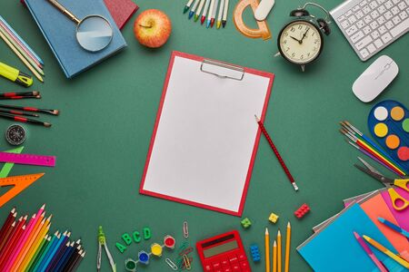 Red clipboard with blank sheet, computer keyboard, calculator and stationery accessories  on green background. Top view, copy space. School accessories for education and development. Office supplies