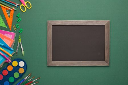 Blank blackboard and stationery accessories on green background. Top view, copy space. School accessories for education and development. Office supplies