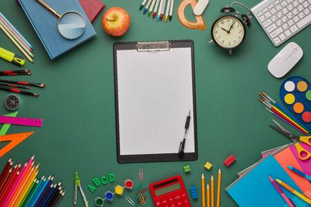 Black clipboard with blank sheet, computer keyboard, calculator and stationery accessories  on green background. Top view, copy space. School accessories for education and development. Office supplies