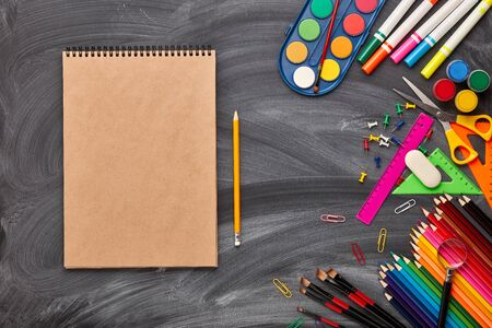 Blank sheet of writing-book and stationery accessories on background of school blackboard. Top view, copy space. School accessories for childrens education and development.  Office supplies.