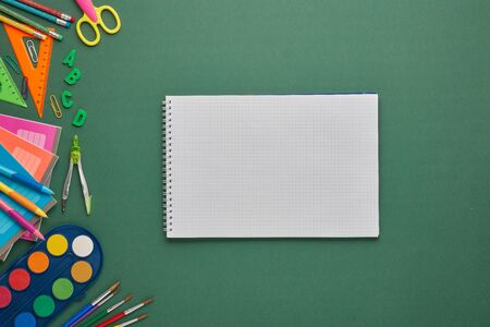 Blank writing-book and stationery accessories on green background. Top view, copy space. School accessories for education and development. Office supplies Zdjęcie Seryjne