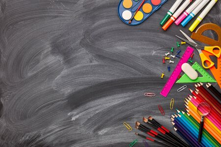 Stationery accessories on background of school blackboard. Top view, copy space. School accessories for childrens education and development.  Office supplies. Zdjęcie Seryjne