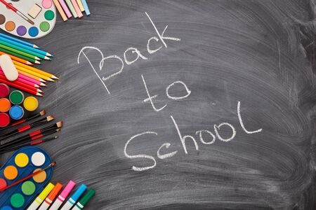 Stationery accessories on background of school blackboard with inscription: Back to school. Top view. School accessories for childrens education and development. Art lesson or drawing Zdjęcie Seryjne