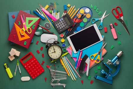 Shopping trolley, computer tablet, calculator, microscope, stationery accessories on green background. Top view, copy space.  School accessories for education and development. Preparation for school