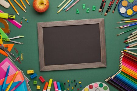 Blank blackboard, apple  and stationery accessories on green background. Top view, copy space. School accessories for childrens education and development. Office supplies. Preparation for school Zdjęcie Seryjne