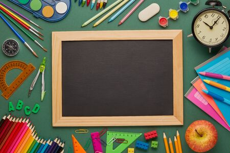 Blank blackboard, alarm clock, apple  and stationery accessories on green background. Top view, copy space. School accessories for education and development. Office supplies