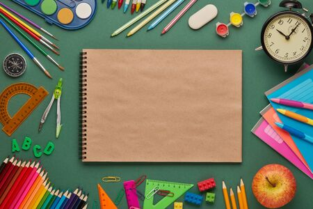 Blank writing-book, alarm clock, apple  and stationery accessories on green background. Top view, copy space. School accessories for education and development. Office supplies 写真素材
