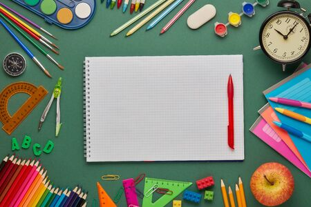 Blank writing-book, alarm clock, apple  and stationery accessories on green background. Top view, copy space. School accessories for education and development. Office supplies Zdjęcie Seryjne