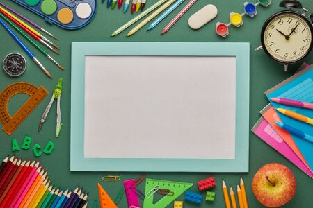 Blue frame with blank sheet, alarm clock, apple  and stationery accessories on green background. Top view, copy space. School accessories for education and development. Office supplies