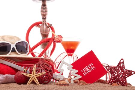 Beach accessories, seashells, sand, glass with cocktail,  hookah (shisha) and christmas ornaments on white background. New Year and Christmas. Winter  vacation  in warm countries, beach holiday