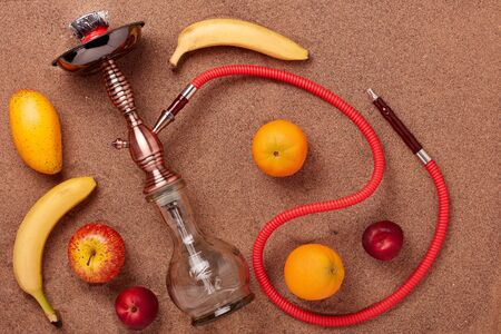 Turkish hookah (shisha) and fruit on a sand background.