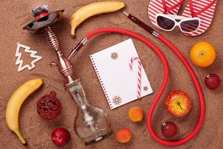 Beach accessories, hookah (shisha), fruit,  blank sheet of notebook and christmas ornaments on sand background. Top view. New Year and Christmas. Winter  vacation  in warm countries, beach holiday Stock Photo