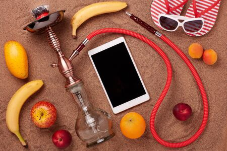 Beach accessories, hookah (shisha), fruit and blank computer tablet on sand background. Top view. Vacation  in warm countries, Beach party and holiday