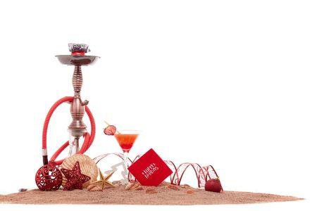 Feestelijk strandstilleven: glas met cocktail, waterpijp (shisha), schelpen, zand en kerstversieringen op witte achtergrond. Nieuwjaar en Kerstmis. Wintervakantie in warme landen, strandvakantie Stockfoto