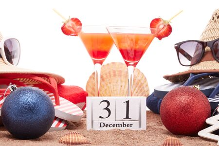 Beach accessories (flip flops, straw hats, seashells, sand, sunglasses), two glasses of cocktail, christmas ornaments on white background. New Year. Winter  vacation  in warm countries, beach holiday