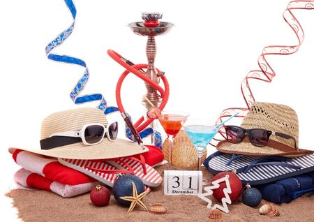 Beach accessories, seashells, sand, two glasses of cocktail,  hookah (shisha) and christmas ornaments on white background. New Year. Winter  vacation  in warm countries, beach holiday Imagens - 128831328