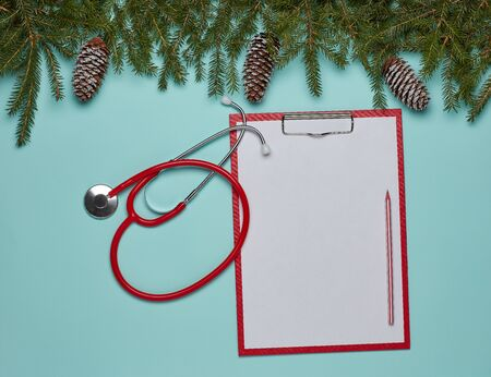 Red stethoscope, blank sheet on clipboard and fir tree branches on green background. Top view with copy space. Medical concept. Greeting card. New Year and Christmas.