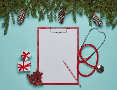 Red stethoscope, blank sheet on clipboard, gift boxes, fir branches and Christmas decorations on green background. Top view with copy space. Medical concept. Greeting card. New Year and Christmas