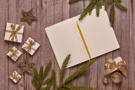 Wooden vintage background with fir tree branches, blank sheets in diary, gift boxes and Christmas ornaments. Top view with copy space. New Year and Christmas,  For greeting card or advertising Reklamní fotografie