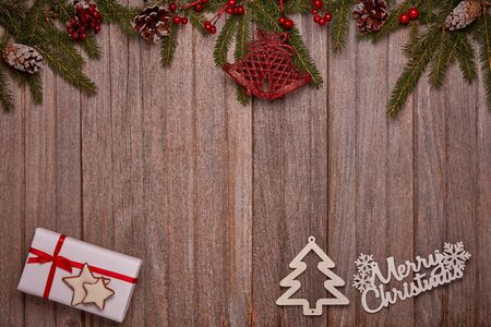 Wooden vintage background with fir tree branches, gift box and Christmas ornaments. Top view with copy space. New Year and Christmas, For greeting card or advertising