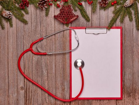 Red stethoscope, blank sheet on clipboard, fir tree  branches and Christmas ornaments on wooden background. Top view with copy space. Medical concept. Greeting card. New Year and Christmas Stok Fotoğraf