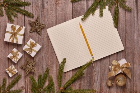 Wooden vintage background with fir tree branches, blank sheets in diary, gift boxes and Christmas ornaments. Top view with copy space. New Year and Christmas,  For greeting card or advertising Reklamní fotografie - 129931248
