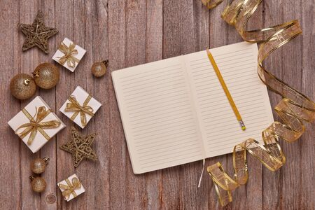 Wooden vintage background with blank sheets in diary, gift boxes and Christmas ornaments. Top view with copy space. New Year and Christmas,  For greeting card or advertising Reklamní fotografie - 129931258
