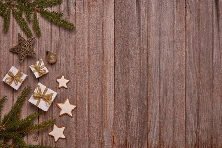 Wooden vintage background with fir tree branches, gift boxes and Christmas ornaments. Top view with copy space. New Year and Christmas,  For greeting card or advertising Reklamní fotografie - 129931263