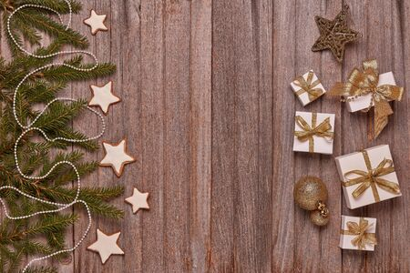 Wooden vintage background with fir tree branches, gift boxes and Christmas ornaments. Top view with copy space. New Year and Christmas,  For greeting card or advertising