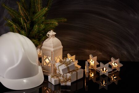 Construction hard hat, candle lantern, gift boxes and Christmas ornament on black background. Construction New Year, Christmas background with copy space. For greeting card or advertising