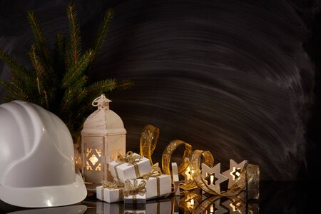 Construction hard hat, candle lantern, gift boxes and Christmas ornament on black background. Construction New Year, Christmas background with copy space. For greeting card or advertising Reklamní fotografie - 129931196