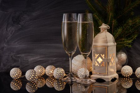 Two wineglasses with champagne, LED lights garland, fir branch, candle lantern on black background with reflection. New Year and Christmas background with copy space. For greeting card or advertising