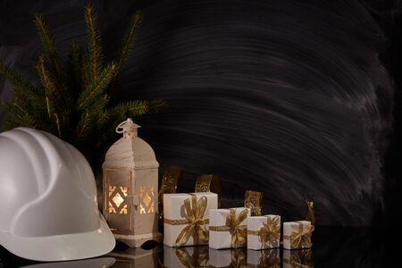 Construction hard hat, candle lantern, gift boxes and fir branch on black background. Construction New Year and Christmas background with copy space. For greeting card or advertising Reklamní fotografie - 129931198