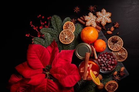 Still life with glasses of mulled wine or fruit tea, Red Poinsettia flowers, fir branch and spices on a dark background. Top view. New year and Christmas table setting. Greeting card. Standard-Bild
